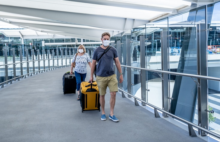 Senior woman and adult son wearing face mask at airport in fear of coronavirus and travel ban and international trips cancellations for disease control and prevention of COVID-19 outbreak pandemic.