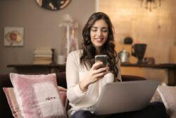 Woman Sitting on Sofa While Looking at Phone With Laptop on Lap